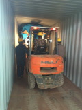 Forklift help to put tractor into container