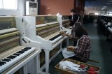 119 white upright piano on production line