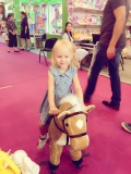 Russian little girl play on the rocking horse at Canton Fair