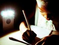 A Child Using a Wakawaka Light in Haiti